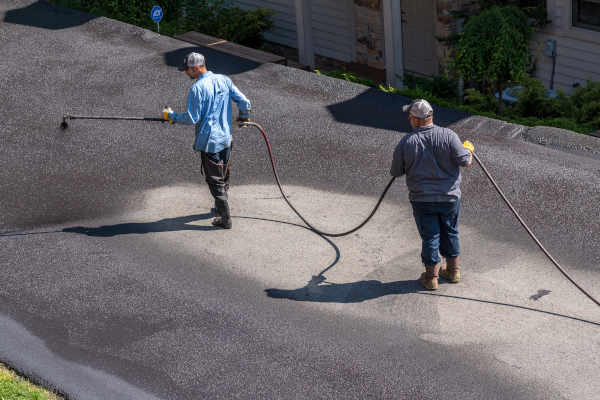 Crew spraying sealcoating on a driveway